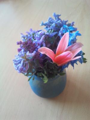 Liten blombukett med lila, blå och en röd blomma.